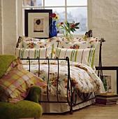 Gestreifte und geblümte Kissen mit floralem Muster auf schmiedeeisernem, antiken Bett vor Fenster mit Bild und Blumen auf Fensterbank