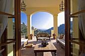 Sofas und ein Holztisch auf der Veranda der spanischen Villa mit Blick auf die Berge