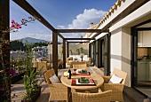 Rattanmöbel auf einem grossen Balkon der spanischen Ferienwohnung mit Blick auf die Berge