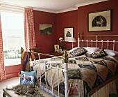 Ein viktorianisches schmiedeeisernes Bett mit Messing in einem roten Schlafzimmer