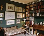 Eine antike Chaiselongue in einem dunkelgrünen Wohnzimmer mit Bücherwand auf der einen Seite