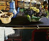Eine alte blaue Emaille-Kaffeekanne, ein Korb mit Fasaneneiern und eine Schale mit Trauben auf einem alten Herd