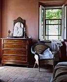 Eingerahmte religiöse Plakette auf einer antiken Kommode in einem toskanischen Schlafzimmer mit traditionellen rosafarbenen Wänden
