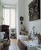 Collage über der Badewanne in einem weissen Badezimmer mit einer Sammlung von Skulptur und Treibholz
