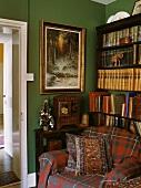 Ein Sessel mit karierter Decke vor dem Bücherregal in einem Wohnzimmer mit grüner Wand