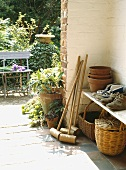 Körbe und Krocket Schläger mit Stiefeln auf dem Regal in der Veranda mit Blick auf Garten