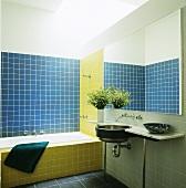 Ein Badezimmer mit blau-gelben Wandfliesen und ein Edelstahlwaschbecken, das unter einen Spiegel in einer Marmorplatte eingebaut ist