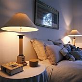 Zwei eingeschaltete Lampen, die an beiden Seiten eines Bettes mit hellgrauen Kissen und Bettwäsche stehen