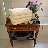 Ein Stapel von weißen Handtüchern und blauen Kornblumen in einem Krug stehen auf einen kleinen antiken Tisch aus Kiefernholz