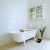 Eine freistehende Badewanne mit Klauenfüßen und ein altes Telefon stehen in der einen Ecke des modernen und weißen Badezimmers