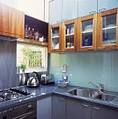 In einer modernen Küche mit einem Edelstahl-Wasserkocher und einen Toaster sind Glas-Einbauschränke über einer Glas Rückwand angebracht worden