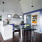 Ein Bar-Tisch, der aus einer Marmorplatte und zwei Stahlzylinder als Tischbeinen besteht, und zwei Barhocker stehen in einer modernen hellen Küche mit einem dunklen Parkettboden