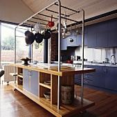 Eine Kücheninsel mit einer Stahlkonstruktion für Küchenutensilien, die aufgehängt werden können
