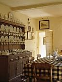 Weißes Porzellangeschirr ist in einer antiken Holzkommode aufgestellt worden, die an einer Wand der weißen Landhausküche mit einem Tisch mit schwarz-weiß karierter Tischdecke