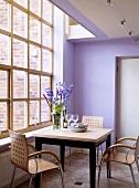 Moderne Holzstühle, die einen quadratischen Tisch umgeben, stehen vor einem großen Fenster des modernen violetten Esszimmers