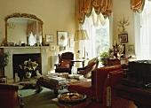In einem Wohnzimmer mit getrimmten apricot Vorhängen hängt ein großer vergoldeter Spiegel über einen Marmorkamin