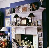 Nahaufnahme eines mit Gegenständen und Familienbildern überladen und weißen Kamins