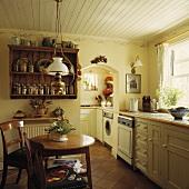 Ein kleiner antiker Kiefer-Tisch und Stühle stehen in einer Küche mit alten Kiefern-Regalen und einer weißen Holzdielendecke