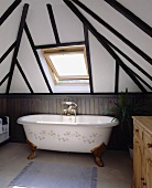 Eine freistehende Badewanne steht unter einem Velux-Dachfenster des Badezimmers eines Fachwerkhauses