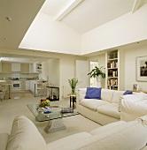 weiße Sofas und ein Glastisch stehen in einer modernen und offenen Wohnung