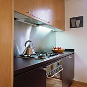 Eine kleine moderne Küche mit Holz-Einheiten und einer Edelstahl Rückwand
