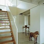 Ein antiker Tisch und eine Holzskulptur des Trojanischen Pferdes stehen in dem modernen weißen Saal mit einer Holztreppe