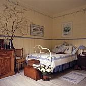 Ein traditionelles Landhaus-Schlafzimmer in dem ein Eisenbett und diverse Holzmöbel stehen