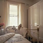 weiße Vorhänge umgeben das Fenster eines weißen Schlafzimmers, das mit einem Eisenbett und einen großen Wandschrank eingerichtet ist