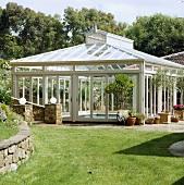 Ein freistehender Glasbau, der das Schwimmbecken im Garten vor Witterung schützt