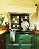 Küche in altem Haus mit grünem Aga-Ofen unter antikem Kaminabzug mit Funktion als Dunstabzugshaube