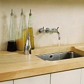 Küchenarbeitsfläche aus Holz mit eingefrästem Ablauf in Edelstahl-Unterbaubecken und moderner Wandarmatur neben Flaschen mit Essig und Öl