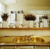 Alte, weisse Emaillekrüge auf Schrank und Küchentheke über genieteter Messingarbeitsfläche mit zwei kreisrunden Spülbecken und antiker Armatur