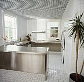 Edelstahl-Einbauschränke in steriler Küche mit weissen Fliesen an Wänden und Boden und weisser Rasterdecke
