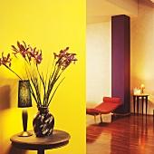 Vase mit Iris auf kleinem Holztisch vor gelber Wand in Kontrast mit lilafarbener Mauersäule und orangefarbener Liege in modernem Wohnzimmer