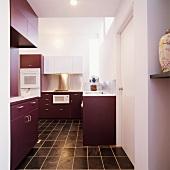 Blick in moderne Einbauküche in Bordeaux und Weiss mit chinesischer Vase auf Wandbord