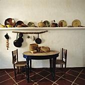 Körbe, Keramikteller und Pfannen auf Wandbord hinter rundem Holztisch mit antiken Stühlen in rustikaler Küche