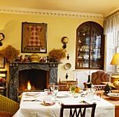 Gedeckter Tisch in Wohnzimmer mit Kaminfeuer und Einrichtung in rustikal-traditionellem Stilmix
