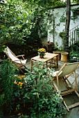 Holzliegestühle mit Tisch auf geschützter Terrasse in Sommergarten