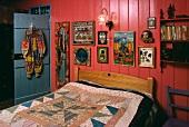 Schlafzimmer mit farbenfrohen Bildern auf rosa Wandtäfelung hinter Bett mit Patchwork-Decke in kleinem Hippie-Landhaus