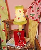 Stoffbeutel und Tischlampe mit gemalten Fruchtmotiven hinter rotem Schmuckkästchen auf hölzernem Kinderstuhl