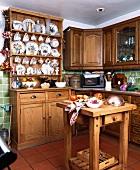 Arbeitsblock und Anrichte aus Kiefer in kleiner, traditioneller Küche mit Sammlung bemalter Teller und Tassen