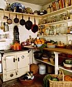 Aufgehängte Pfannen über weißem Rayburn Ofen in einfacher Küche mit offenen, beladenen Regalen