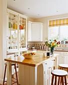 Moderne Küche mit weiss lackierten Fronten, Naturholz-Arbeitsflächen und Küchenblock als Frühstücksbar