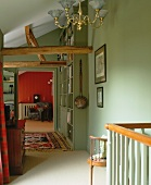Rustikale Holzbalken in Kontrast mit traditionellem, sanft grünem Treppenflur mit Bücherwand