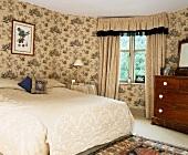 Tagesdecke und Schabraken-Vorhang aus hell geprägtem Stoff und helle, mit grünen Motiven bedruckte Toile-de-Jouy Tapete in klassischem Schlafzimmer