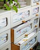 Bestickte Stoffe in Schubladen mit Glasfronten in weißem, altem Küchenschrank