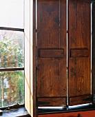 Halb geöffneter, schlichter Fensterladen vor Fenster aus georgianischer Zeit