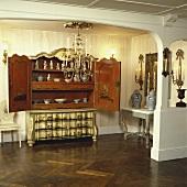 Ein Kronleuchter und eine antike orientalische Anrichte mit geöffneten Türen in einer ländlichen Halle mit Parkettboden