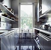Metallhocker vor einem hohen Fenster in der modernen Küche mit Edelstahl-Einbauschränken