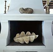 Ein weisser Kamin mit einer Ammonite und einer großen Muschel